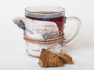 Chagapilz Tee in einem Glas auf weissem Grund